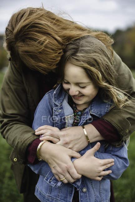 Мать и дочь обнимаются на лугу — стоковое фото
