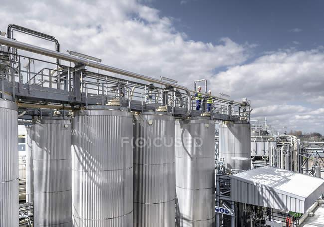 Trabalhadores em cima da planta de processo na fábrica de mistura de óleo — Fotografia de Stock