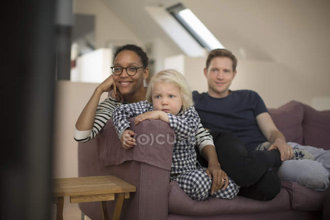 Family sitting on sofa watching television at home — Stock Photo