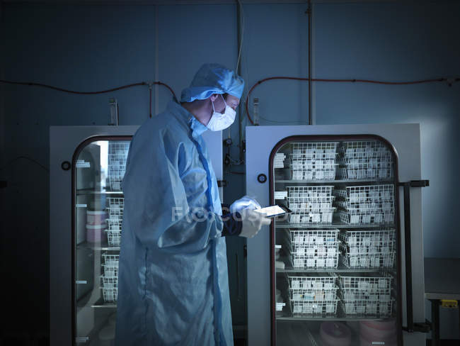 Worker using digital tablet to check archived electronic components in nitrogen atmosphere in clean room laboratory — Stock Photo