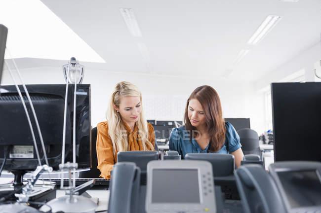 Travailleurs de bureau féminins adultes de mi au bureau — Photo de stock