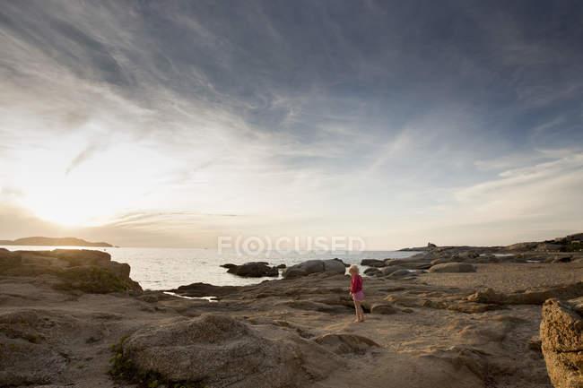 Femme enfant en bas âge sur un rocher côtier au coucher du soleil, Calvi, Corse, France — Photo de stock