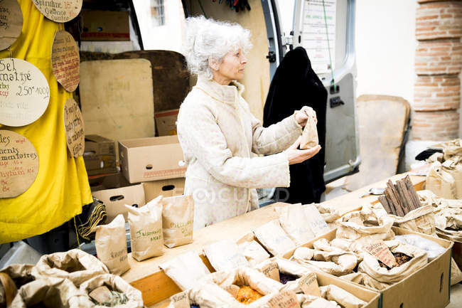 Mature female stall holder selling dried foods at local french market — Stock Photo