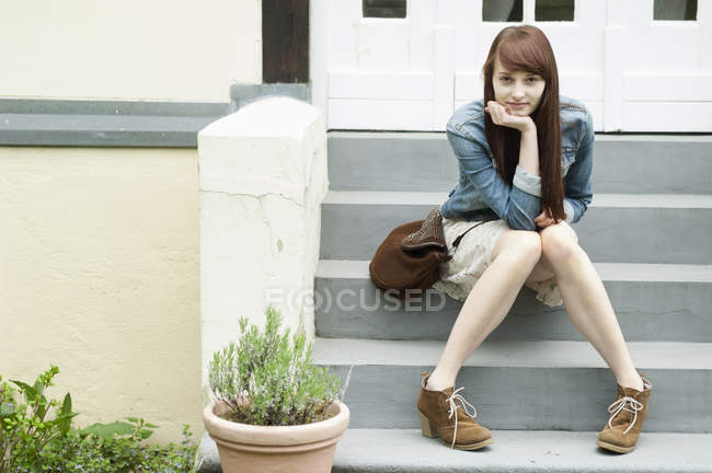Portrait of young woman sitting on house steps — Stock Photo