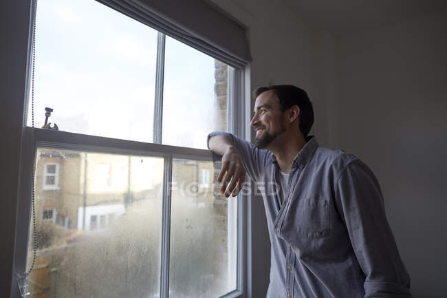 Mid adult man looking out through bedroom window — Stock Photo