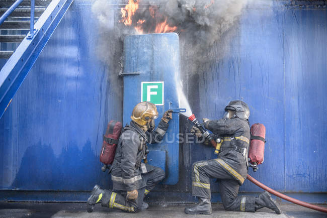 Firefighters tackling flames behind steel door in fire simulation training facility — Stock Photo