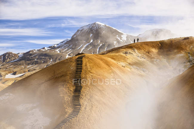 Distant view of two hikers on mountain surrounded by geothermal steam — Stock Photo