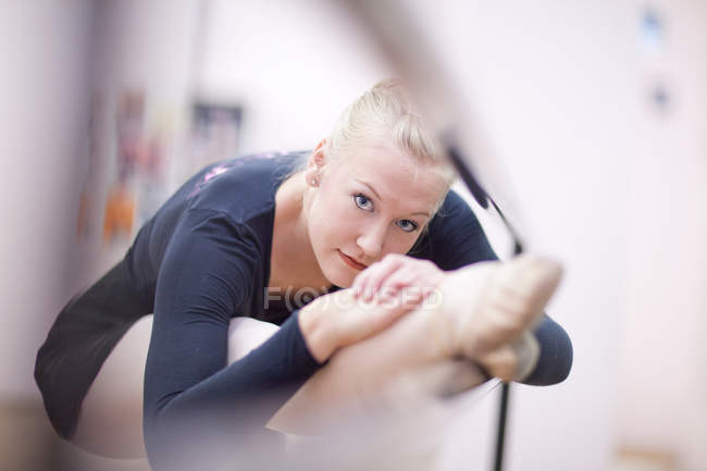 Portrait of female ballerina practicing at the barre — Stock Photo