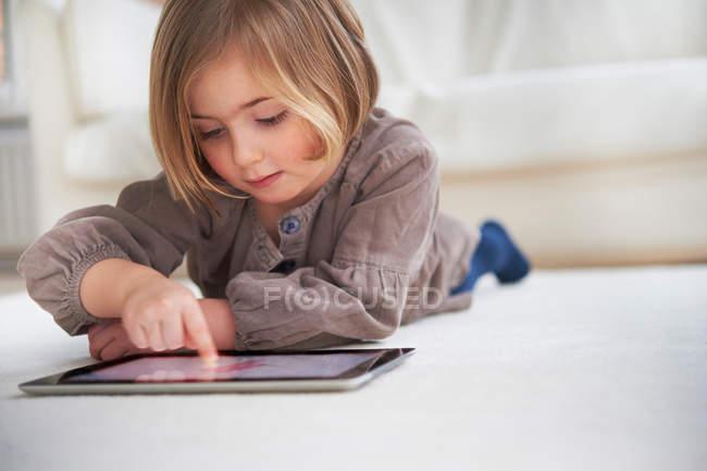 Ragazza sdraiata sul pavimento e utilizzando tablet digitale — Foto stock
