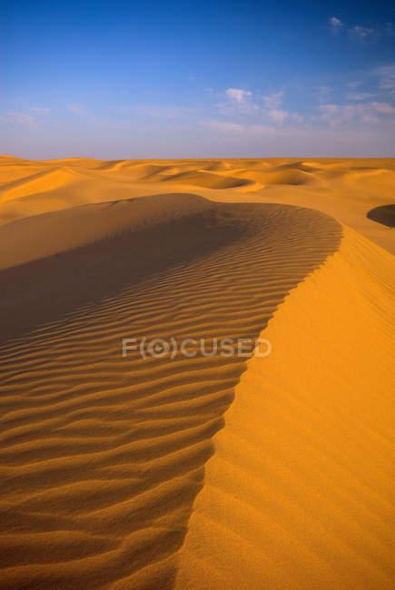 Rippled dunas de areia do deserto do Namibe, sob o céu azul — Fotografia de Stock