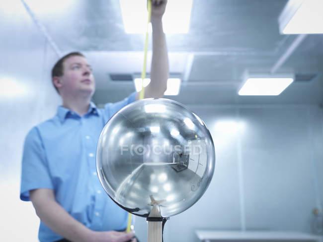 Ingeniero de comprobación de la altura del equipo bajo prueba (Eut) con Van Der Hoofden Head utilizado durante las pruebas de seguridad de campo electromagnético (Emf) de iluminación electrónica en primer plano - foto de stock