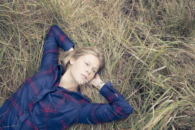Vue aérienne de la jeune femme allongée dans une longue herbe — Photo de stock