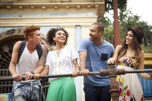 Small group of friends holding onto railing, smiling — Stock Photo