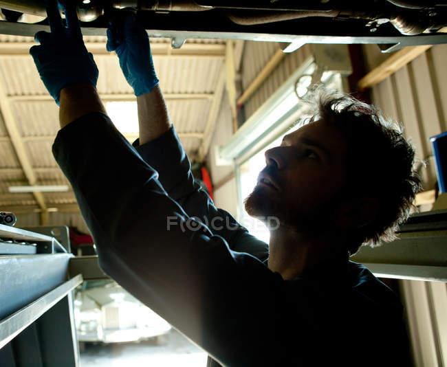 Мужчина-механик под машиной, ищет проблему — стоковое фото
