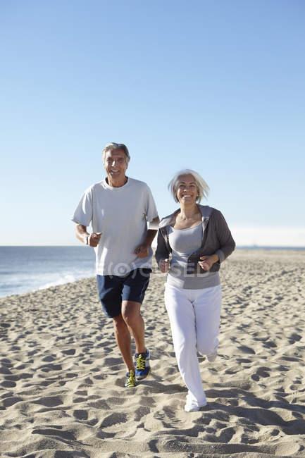 Casal jogging na praia — Fotografia de Stock