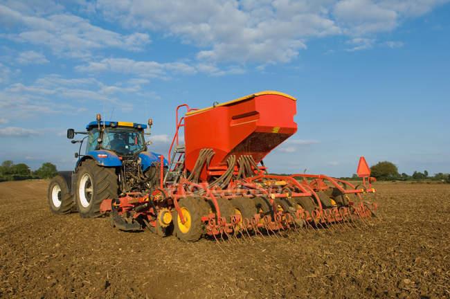 Fermier conduisant le tracteur et le forage de maïs de semence dans le champ — Photo de stock