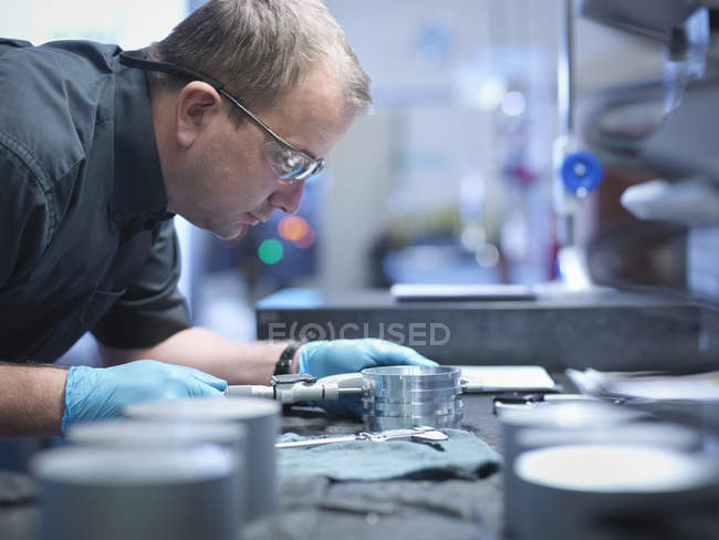Portrait of engineer measuring engineered part in factory — Stock Photo