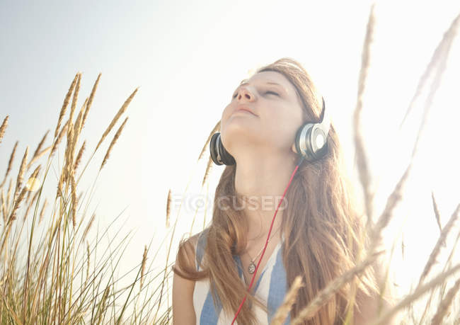 Teenage girl listening to music outdoors — Stock Photo