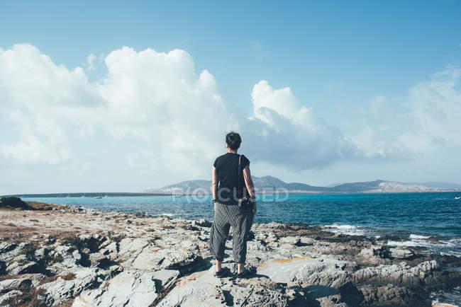Rear view of woman on rocks looking sea, Stintino, Sassari, Italy — стоковое фото
