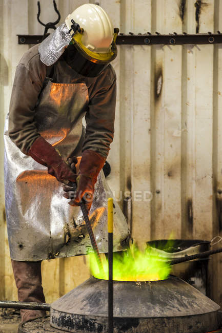 Male foundry worker working with green flamed furnace in bronze foundry — Stock Photo