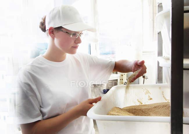 Бейкер, дивлячись на зерно — стокове фото