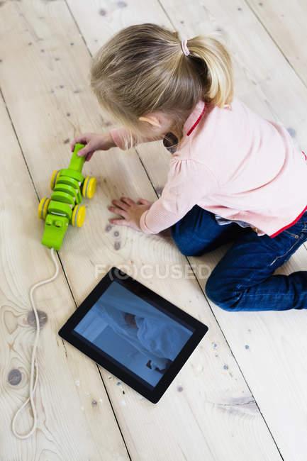 Chica con tableta digital, juegan el juguete en el piso de madera - foto de stock