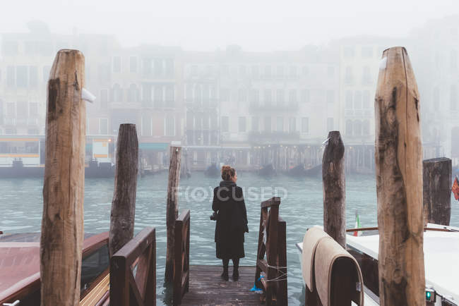 Rear view of woman looking out from misty canal pier, Venice, Italy — Stock Photo
