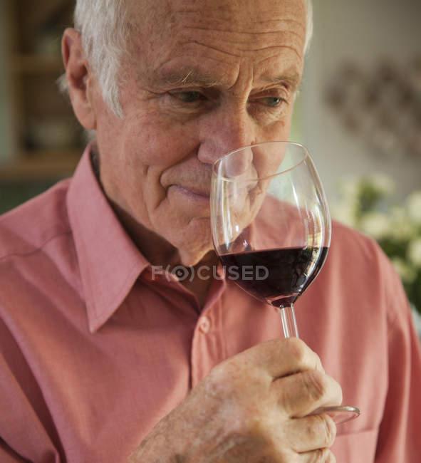 Homme sentant arôme de verre de vin rouge — Photo de stock