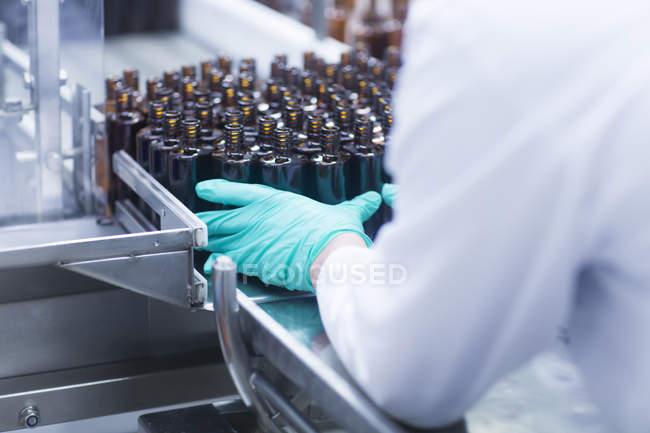 Обрезанное изображение мужской руки в перчатке с бутылками — стоковое фото