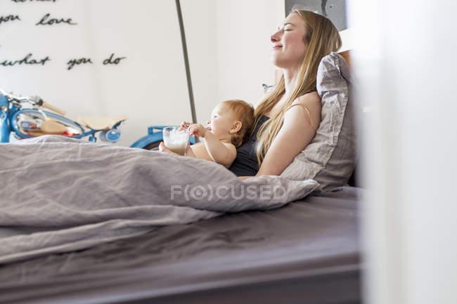 Donna stanca e bambina sdraiata a letto con caffè — Foto stock