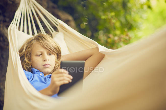Boy reclining in garden hammock browsing digital tablet — Stock Photo