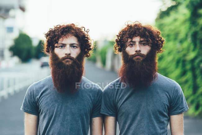 Портрет идентичных взрослых близнецов-мужчин с рыжими волосами и бородами на тротуаре — стоковое фото