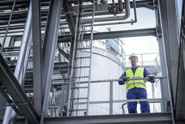 Worker on top of process plant in oil blending factory, low angle view — Stock Photo