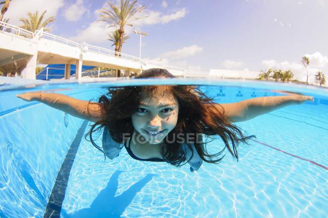 Mergulho livre da menina a água na piscina — Fotografia de Stock