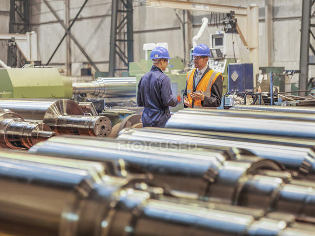 Manager and worker in discussion in engineering factory — Stockfoto