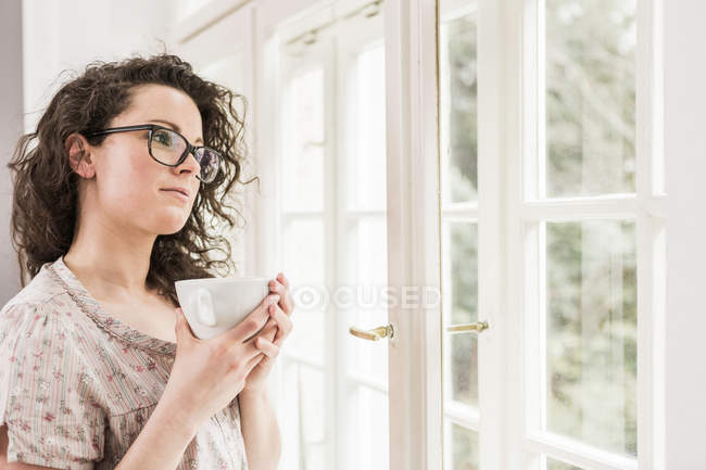 Mid adult woman holding coffee cup, looking out of window — Stock Photo