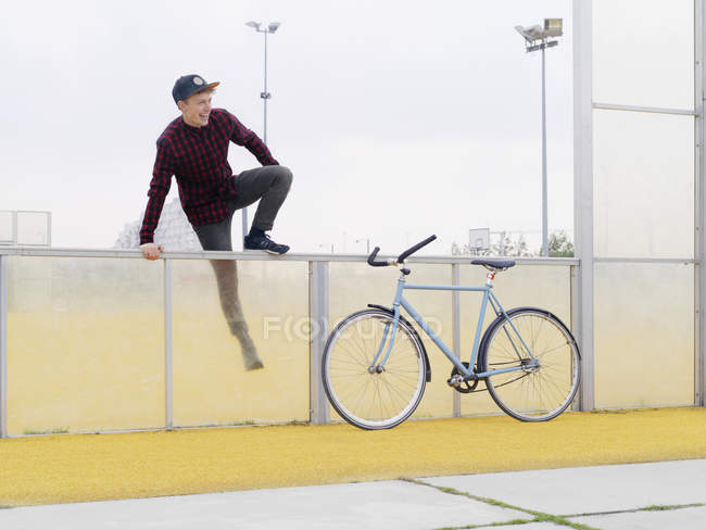 Urban cyclist climbing over fence on sports field — Stock Photo