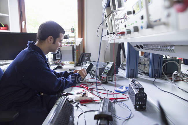 Male electrician repairing electronic equipment in workshop — Stock Photo