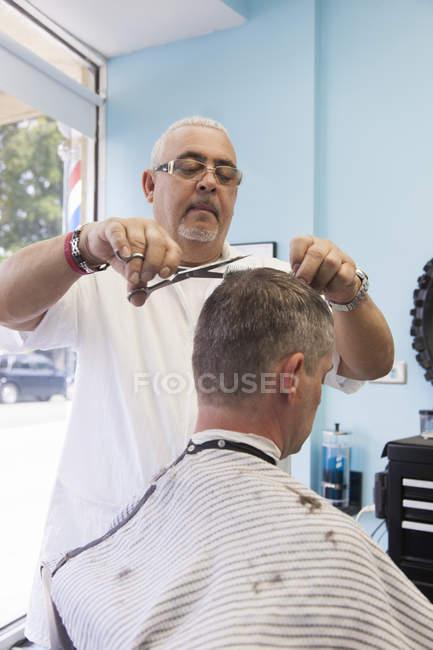 Парикмахер стрижет волосы клиента в салоне — стоковое фото