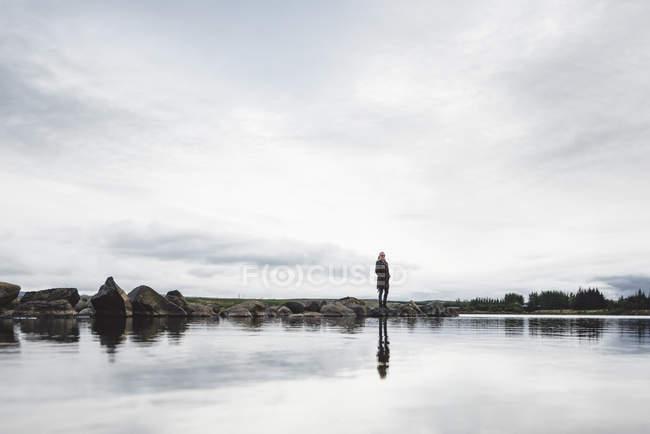 Donna in piedi sul bordo dell'acqua, Hafravatn, Islanda — Foto stock