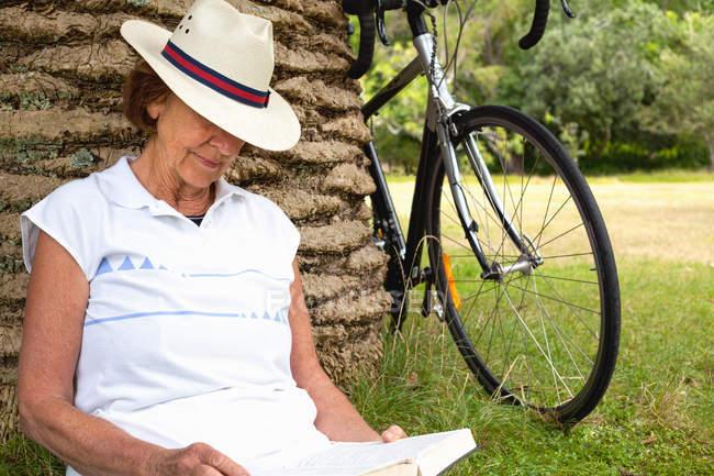 Donna anziana appoggiata alla lettura delle palme nel parco — Foto stock