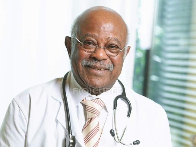 Старший лікаря з стетоскоп, носіння лабораторний халат — стокове фото