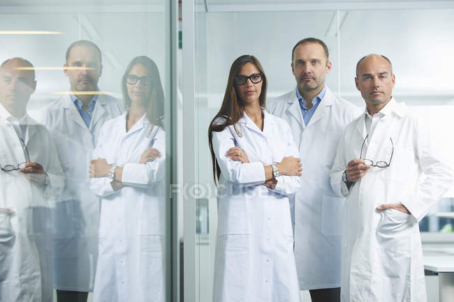 Team of female and male doctors posing for camera — Stock Photo