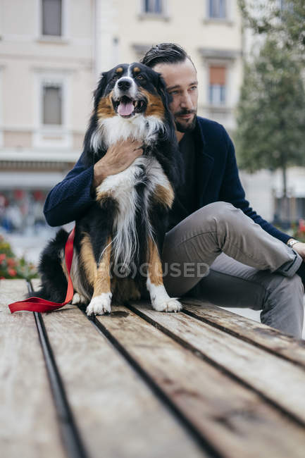 Mid adult man sitting with pet dog on city square bench — Stock Photo