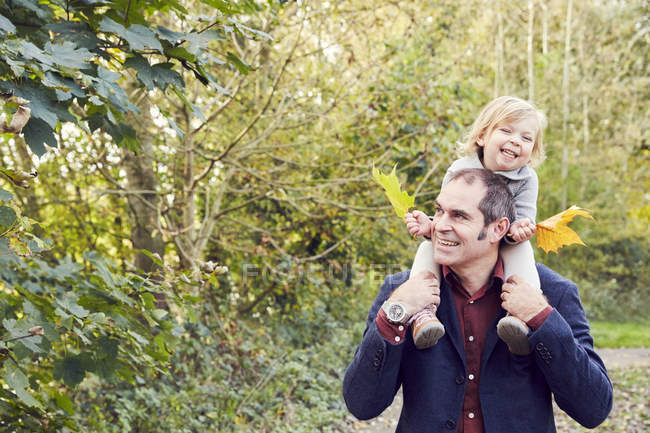Father carrying daughter on shoulders in autumn park — Stock Photo