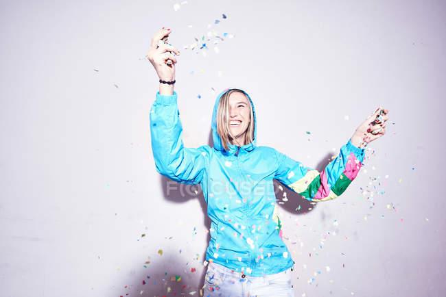Estudio de tiro de mujer joven lanzando confeti - foto de stock