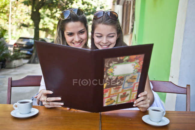 Female friends looking at cafe menu together — Stock Photo