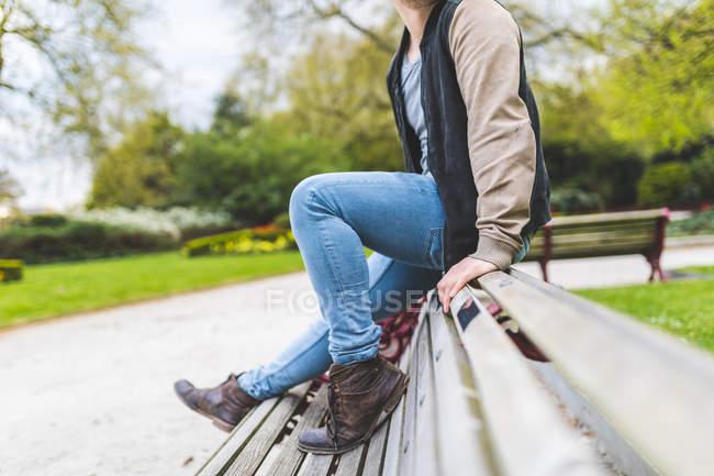 Pescoço para baixo a visão do jovem sentado no banco em Battersea Park — Fotografia de Stock
