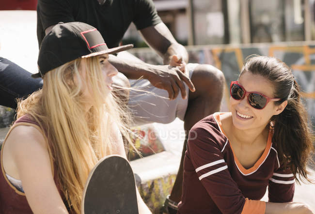 Two female friends chatting in city skatepark — Stock Photo