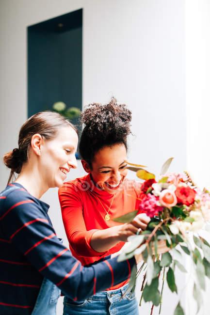 Двоє усміхнених жінок, що роблять букет в магазині флористів — стокове фото